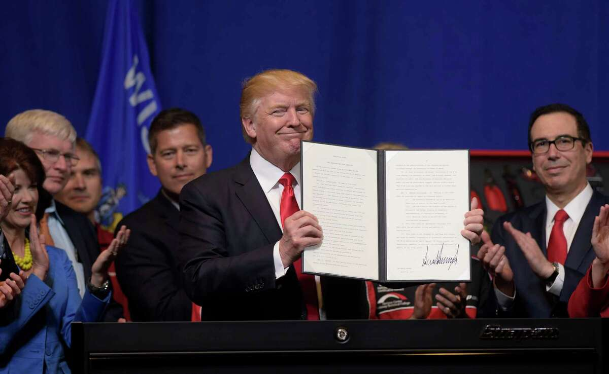 """FILE - In this April 18, 2017 file photo, President Donald Trump holds up the """"Buy American, Hire American"""" executive order which he signed during a visit to the headquarters of tool manufacturer Snap-on Inc. in Kenosha, Wis. Immigrants with specialized skills are being denied work visas or seeing applications get caught up in lengthy bureaucratic tangles under federal changes that some consider a contradiction to Trump?'s promise of a continued pathway to the U.S. for the best and brightest. (AP Photo/Susan Walsh)"""