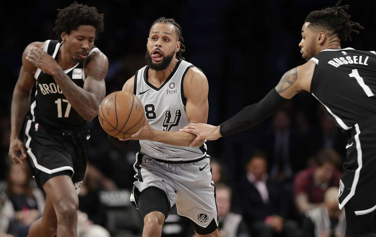 Brooklyn Nets guard D'Angelo Russell (1) grabs the arm of San Antonio Spurs guard Patty Mills (8) during the first half of an NBA basketball game, Monday, Feb. 25, 2019, in New York. (AP Photo/Kathy Willens)