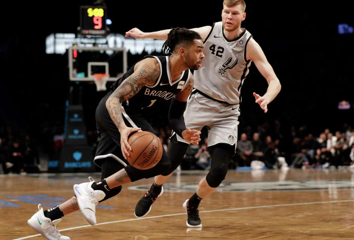 San Antonio Spurs forward Davis Bertrans (42) defends Brooklyn Nets guard D'Angelo Russell (1) who drives to the basket during the second half of an NBA basketball game, Monday, Feb. 25, 2019, in New York. The Nets defeated the Spurs 101-85. (AP Photo/Kathy Willens)