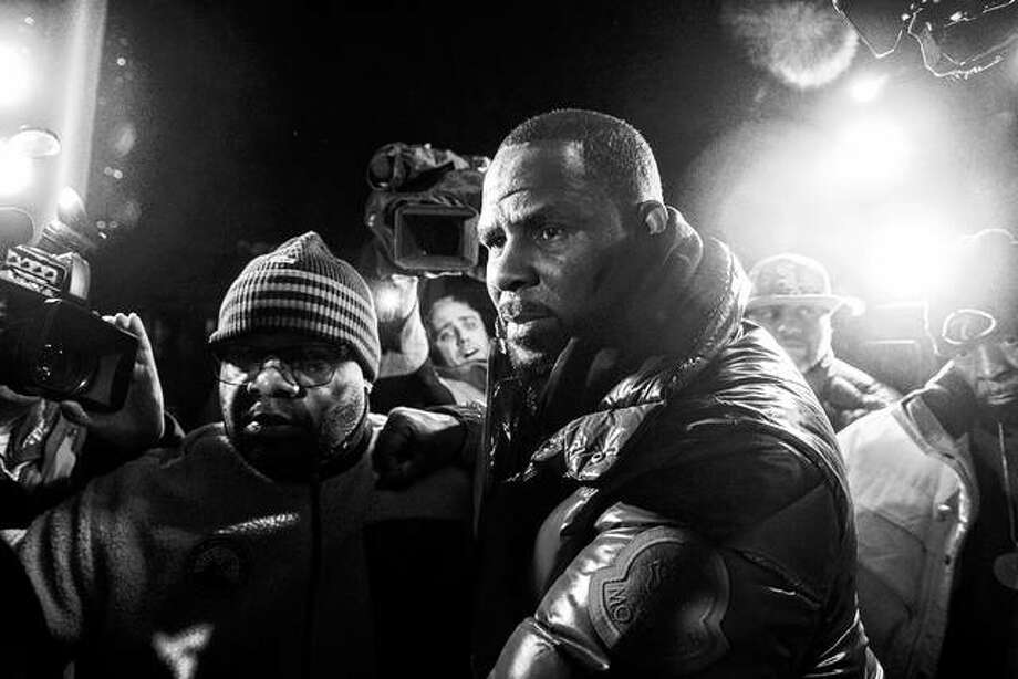 R. Kelly surrenders Friday to authorities at Chicago First District police station. The R&B star was taken into custody after arriving Friday night at a Chicago police precinct, hours after authorities announced multiple charges of aggravated sexual abuse involving four victims, including at least three between the ages of 13 and 17. Photo: Tyler LaRiviere | Chicago Sun-Times Via AP