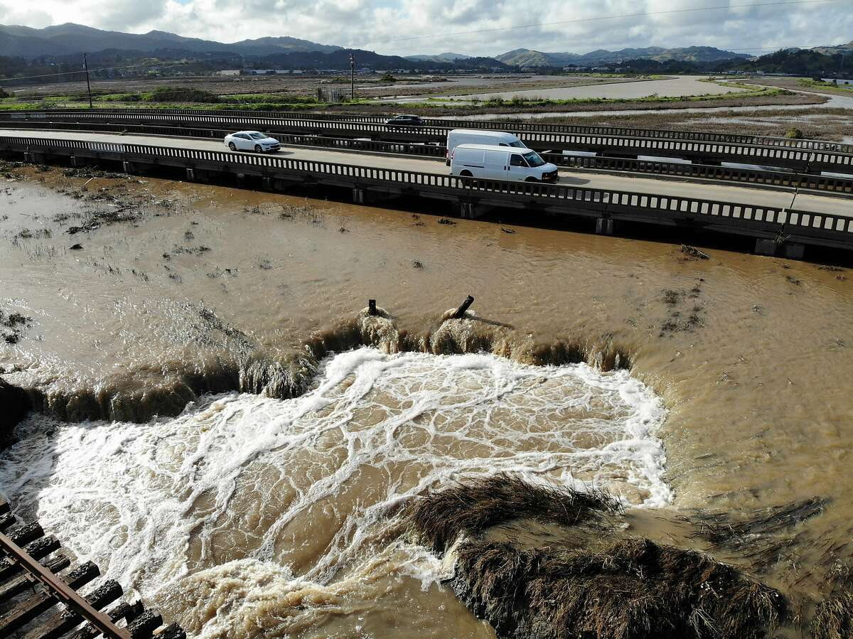 Water from recent heavy rain storms breeches a levee in Novato, Calif., Thursday, Feb. 14, 2019. Waves of heavy rain pounded California on Thursday, flooding streets, triggering a mudslide that destroyed homes and forcing residents to flee communities scorched by wildfires last year. (AP Photo/Terry Chea)