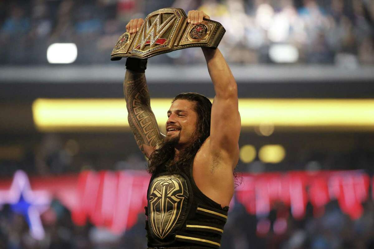 FILE - In this April 3, 2016 file photo, Roman Reigns holds up the championship belt after defeating Triple H during WrestleMania 32 at AT&T Stadium in Arlington, Texas. (Jae S. Lee/The Dallas Morning News via AP)