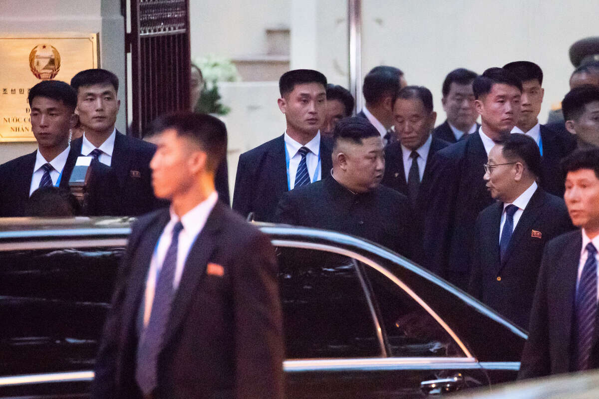 Notth Korea's Kim Jong Un, center, is surrounded by bodyguards as he arrives at the North Korean embassy in Hanoi, on Feb. 26.