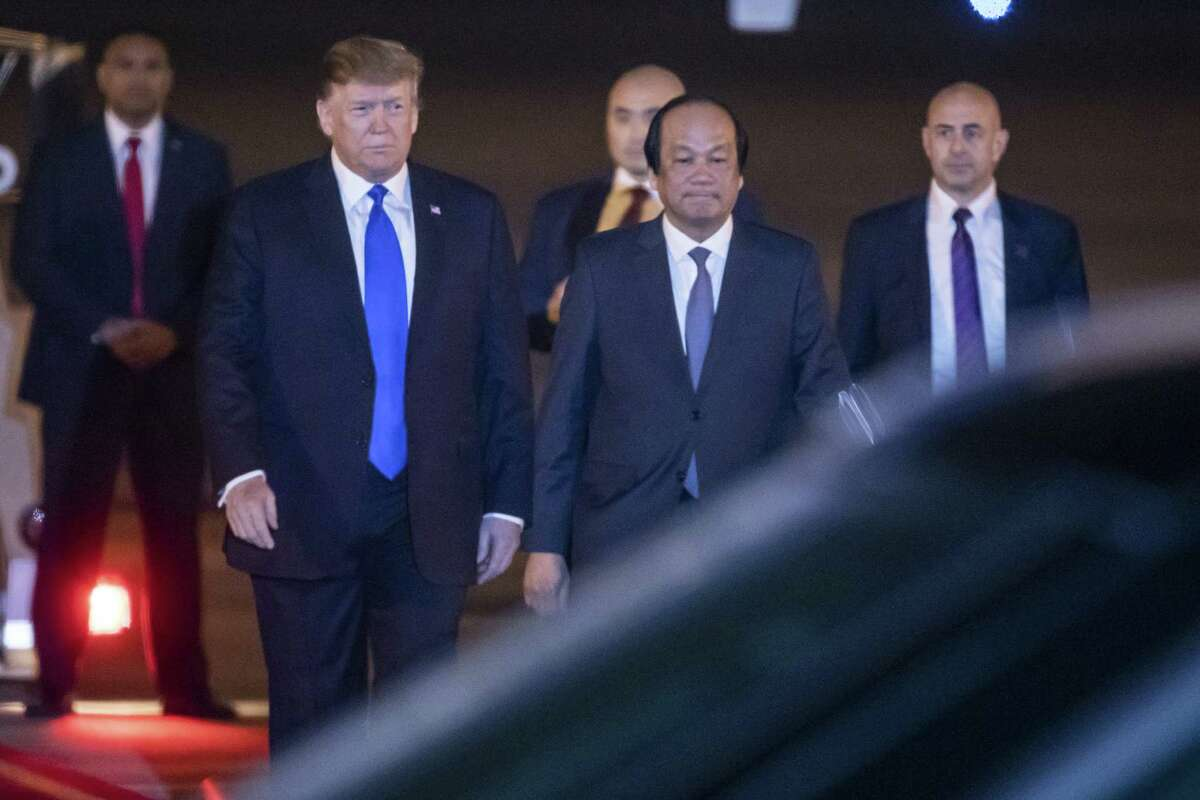 President Donald Trump, left, walks on the tarmac after disembarking from Air Force One after arriving at Noi Bai International Airport in Hanoi on Tuesday, Feb. 26, 2019,