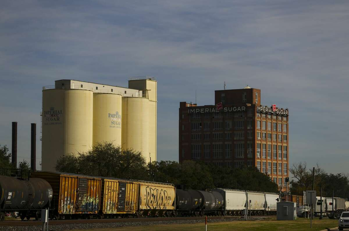 A train passes in front of the old Imperial Sugar refinery in Sugar Land.