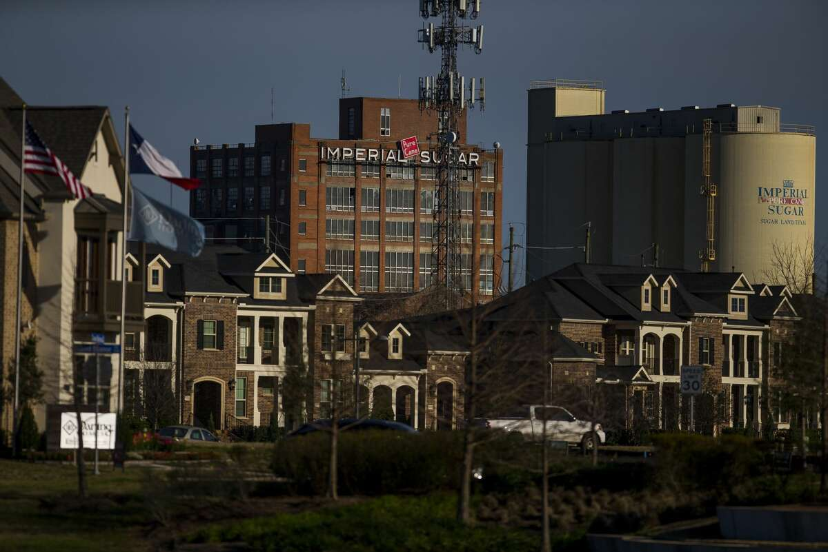 The old Imperial Sugar factory looms over townhouses in the Imperial Sugar Land development. The building has been vandalized and development plans delayed.
