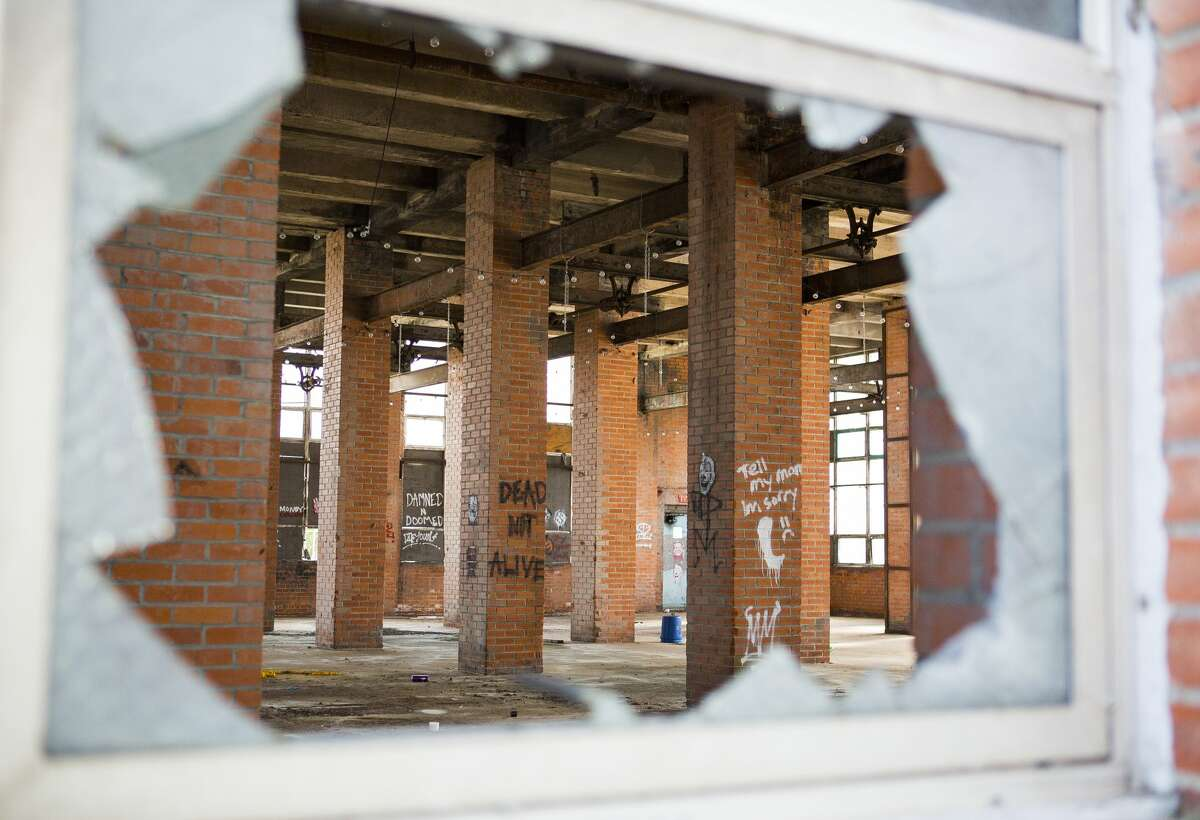 A broken window provides a look into one of the buildings that comprised the Imperial Sugar refinery in Sugar Land.