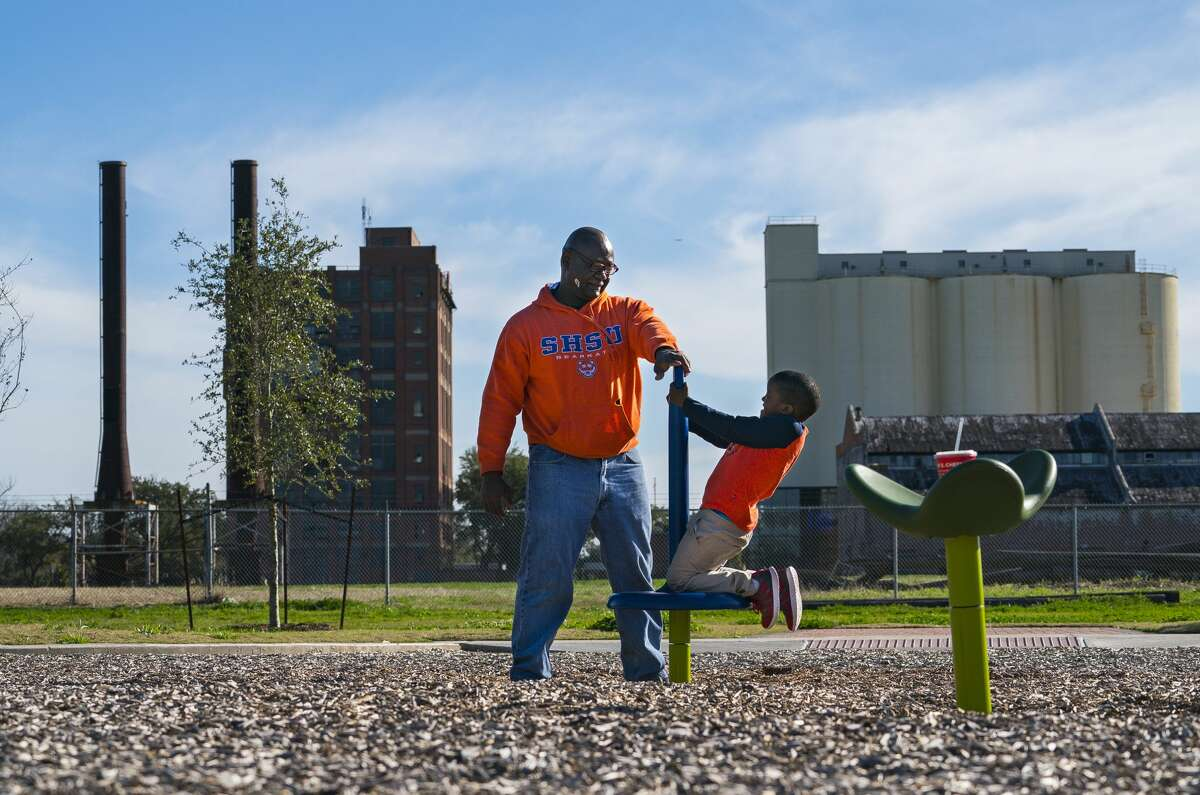 Logene Upson plays with his son Wesley behind the old Imperial Sugar factory that the State Land Board has tried for years to develop into an upscale hotel, with surrounding retail, offices and fine dining.