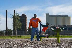 Logene Upson plays with his son Wesley behind the old Imperial Sugar factory that the State Land Board has tried for a dozen years to develop into an upscale hotel, with surrounding retail, offices and fine dining.