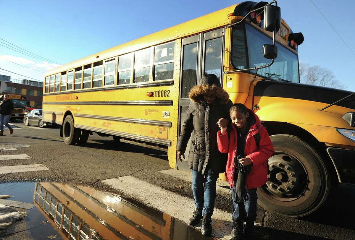 Sy Mercer, of Bridgeport, walks with her son, Micah Daley, 6, as he gets off the bus from Columbus Magnet School outside the new Claytor School on Wordin Avenue in Bridgeport, Conn. on Wednesday, January 27, 2016.