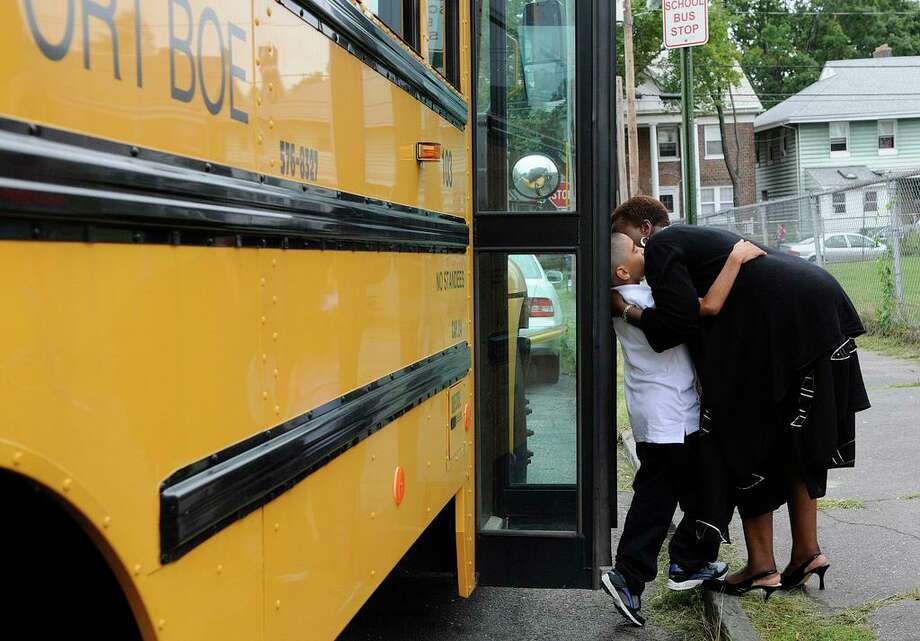 Hall School principal Veronica Thomas and fourth-grader Joshua Martinez greet each other as he steps off the school bus on the first day of school in Bridgeport, CT on Wednesday August 25, 2010. Photo: Shelley Cryan / ST / Shelley Cryan Freelance