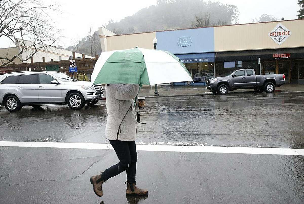 A woman walks on San Anselmo Avenue during the heavy rainstorm in San Anselmo, Calif. on Tuesday, Feb. 26, 2019.