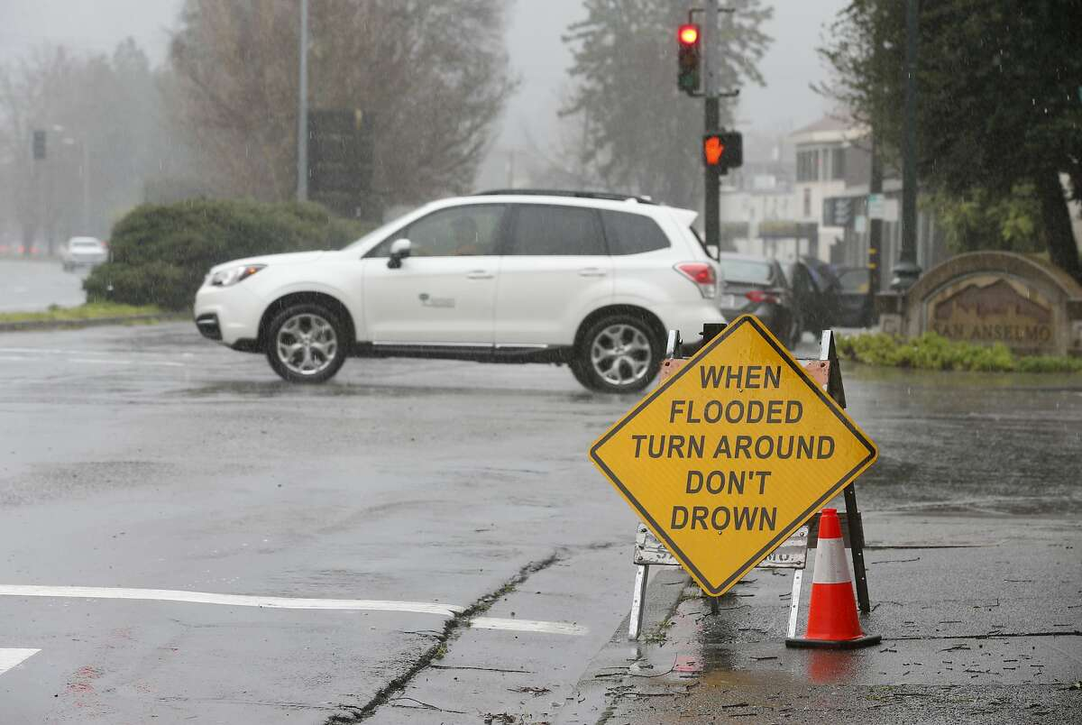 Road signs warn motorists of potential flooding during the heavy rainstorm in San Anselmo, Calif. on Tuesday, Feb. 26, 2019.
