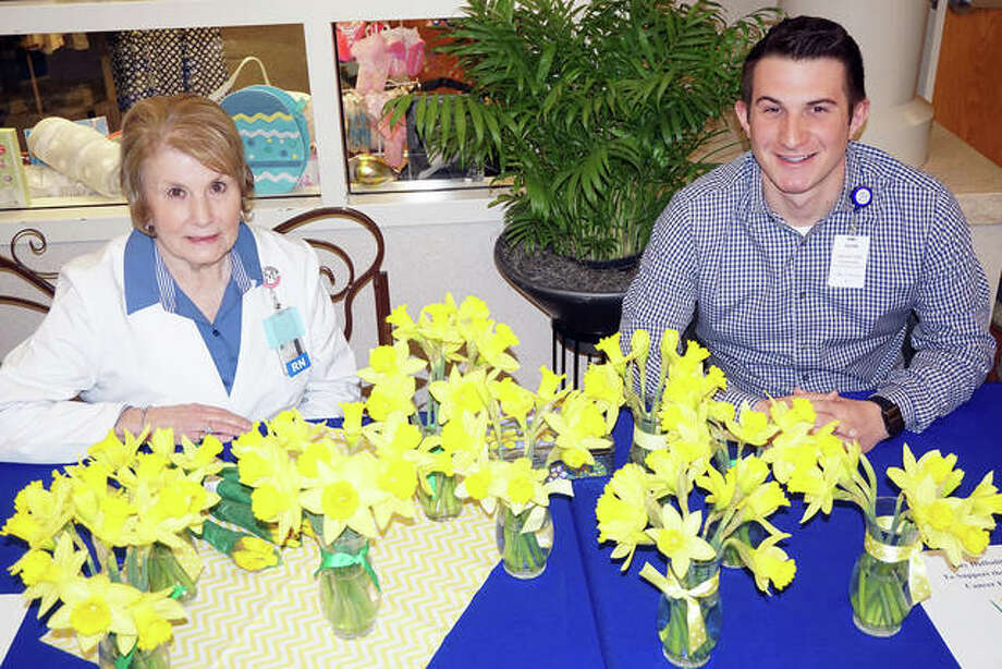 Mary Bayer of Twin Rivers MRI and Adam Mathews of the AMH Medical Staff Office sell flowers during a recent Daffodil Days sale at Alton Memorial Hospital. Photo: For The Telegraph