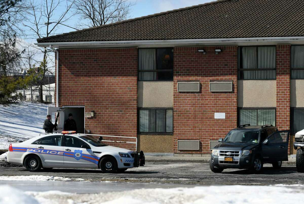 The getaway vehicle, right, used in a North Greenbush bank robbery is parked in the rear of a Motel 6 hotel on Watervliet Ave. Ext. on Tuesday, Feb. 26, 2019, in Albany, N.Y. (Will Waldron/Times Union)
