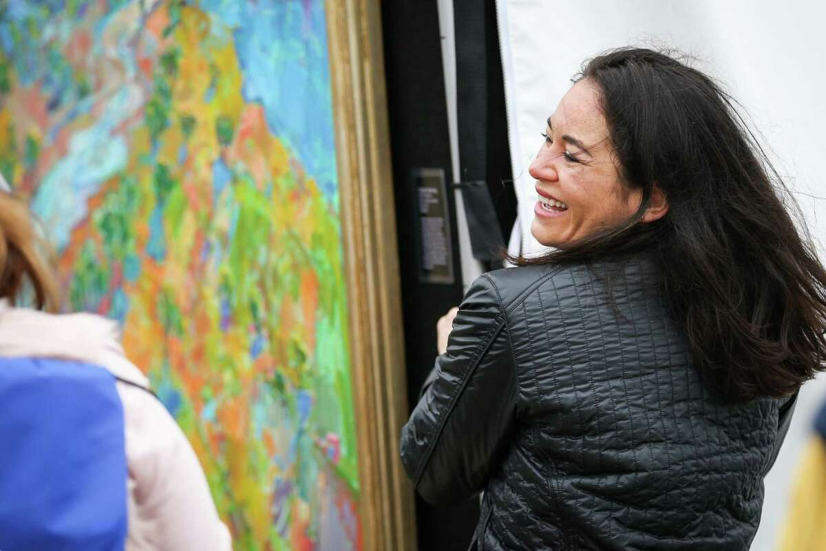 Featured artist Erin Hanson, from San Diego, California, laughs while securing one of her paintings against the wind during The Woodlands Waterway Arts Festival on Saturday, April 7, 2018, in The Woodlands. This year's festival is set for April 13 and 14.