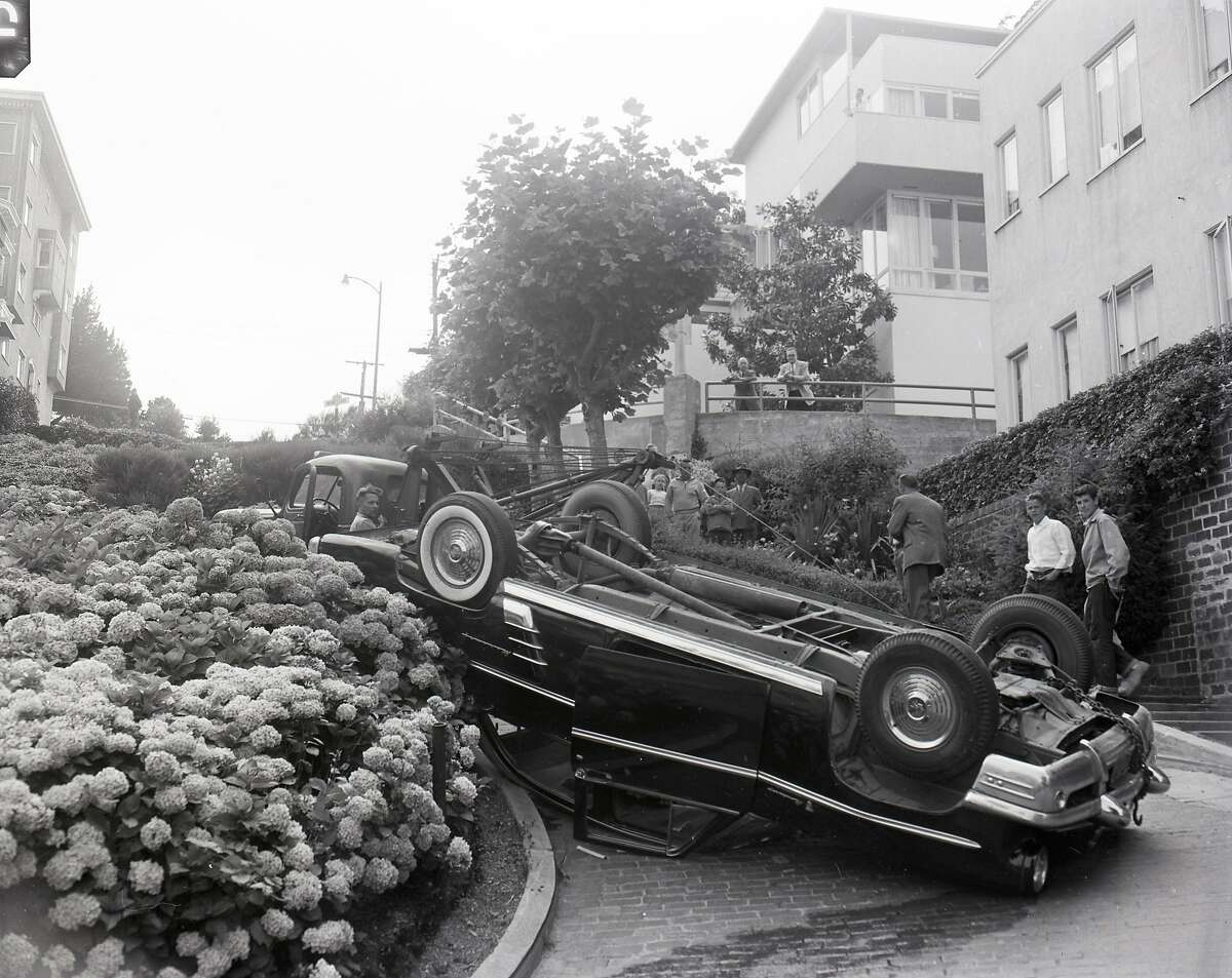 An auto flips over on Lombard Street, known as the crookedest street in the world, August 7, 1956