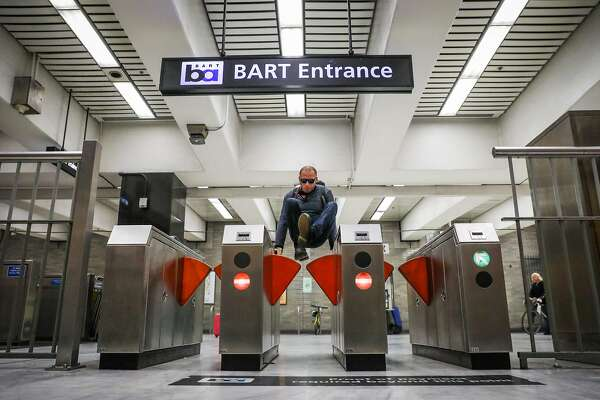 A man jumps the turnstile at the BART station at Civic Center despite gates that were installed (seen at left and right) to deter fare evasion in San Francisco, California, on Thursday, Aug. 16, 2018.