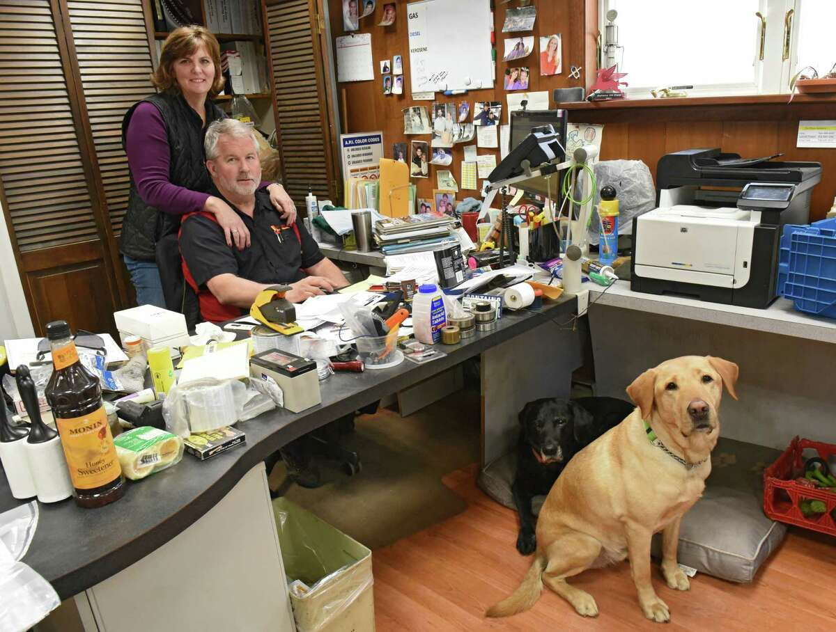 Steve Doheny and his wife Nan are seen in their office at Doheny's service station on Tuesday, Feb. 26, 2019 in Ballston Spa, N.Y. After six decades, the family-owned Doheny's service and gas station is closing down. Their dogs River, under desk, and Barton are usually seen in the office. (Lori Van Buren/Times Union)