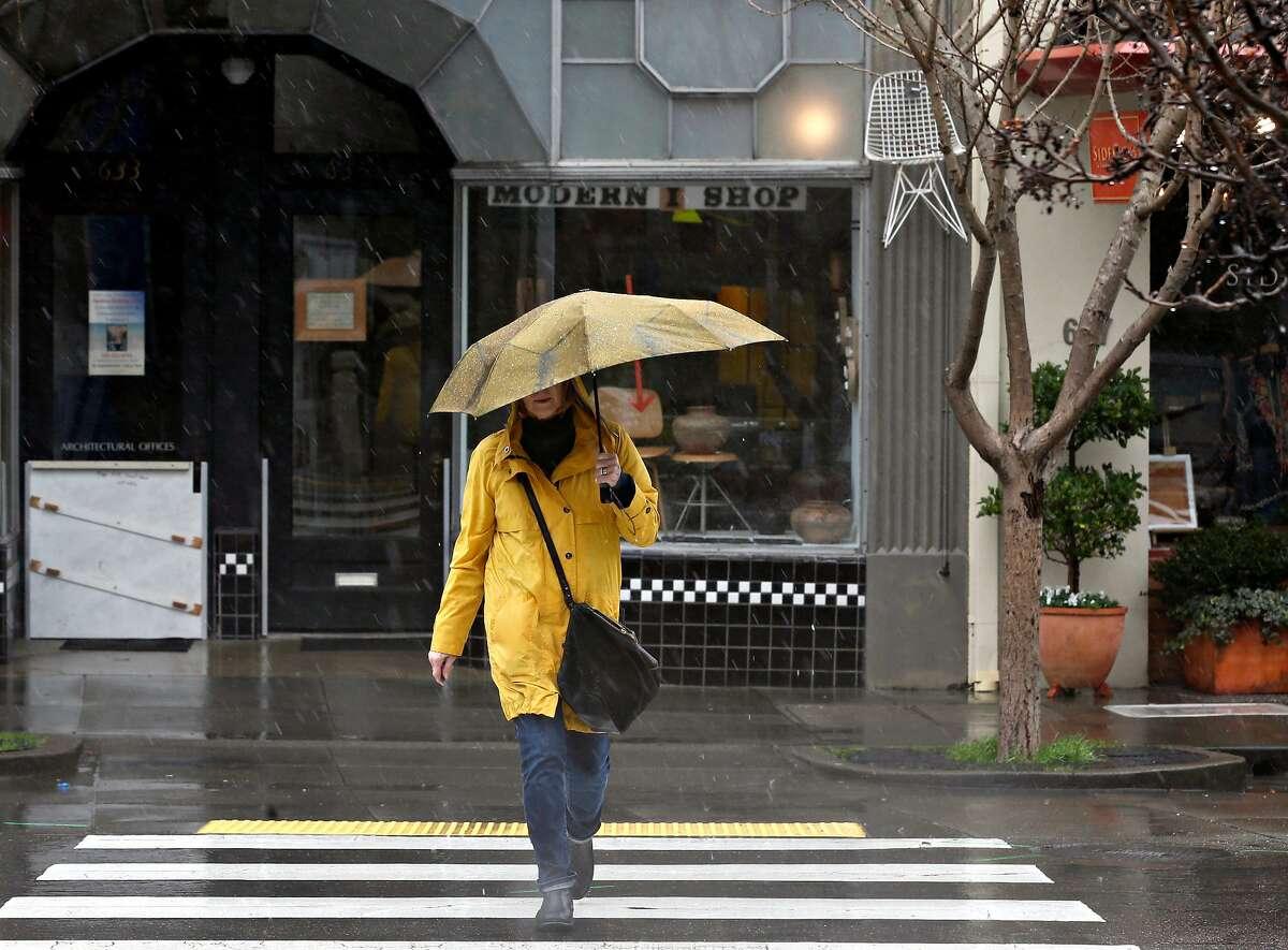 A woman crosses San Anselmo Avenue during the heavy rainstorm in San Anselmo, Calif. on Tuesday, Feb. 26, 2019.