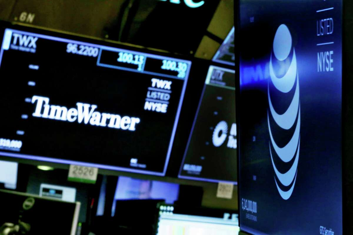 FILE - In this June 13, 2018, file photo, the logos for Time Warner and AT&T appear above alternate trading posts on the floor of the New York Stock Exchange. A federal appeals court has blessed AT&T's takeover of Time Warner, Tuesday, Feb. 26, 2019, defeating the Trump administration by affirming that the $81 billion merger won't harm consumers or competition in the booming pay TV market. (AP Photo/Richard Drew, File)