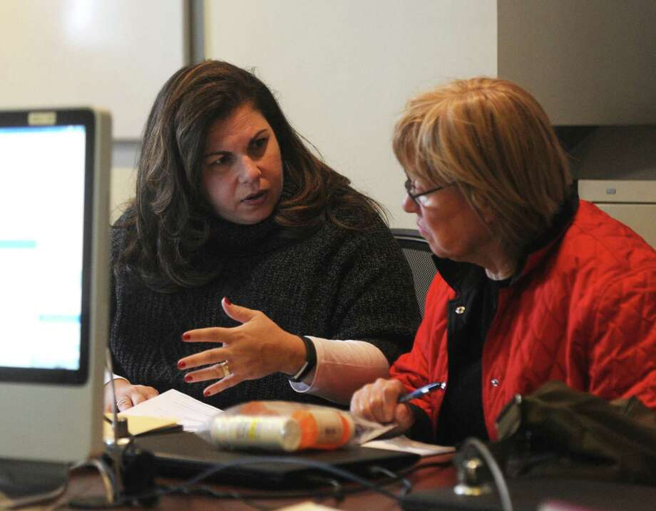 Greenwich Commission on Aging Director Lori Contadino, left, assists a Greenwich resident with Medicare paperwork at the Senior Center in Greenwich, Conn. Monday, Nov. 27, 2017. Photo: File / Tyler Sizemore / Hearst Connecticut Media / Greenwich Time