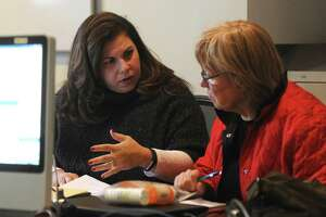 Greenwich Commission on Aging Director Lori Contadino, left, assists a Greenwich resident with Medicare paperwork at the Senior Center in Greenwich, Conn. Monday, Nov. 27, 2017.