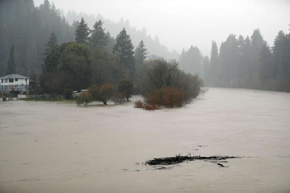 Debris flows down the Russian River a sit rises towards flood stage in Monte Rio, Calif., on Tuesday, February 26, 2019.