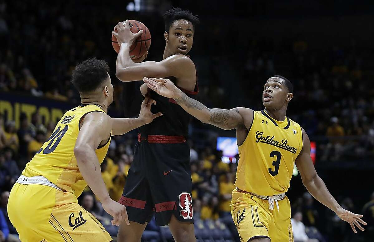 Stanford's KZ Okpala, center, keeps the ball from California's Matt Bradley, left, and Paris Austin (3) in the first half of an NCAA college basketball game Sunday, Feb. 3, 2019, in Berkeley, Calif. (AP Photo/Ben Margot)