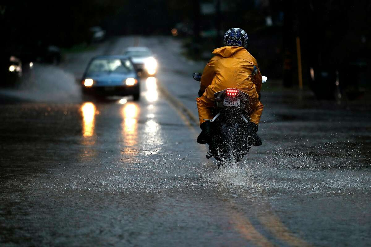 A motorcyclist drives through standing water on Drake Road as the Russian River rises towards flood stage in Guerneville, Calif., on Tuesday, February 26, 2019.