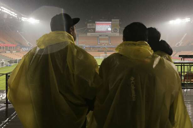 Soccer fans try to stay dry during a rain delay for the Amilcar Cuyuch, left, puts on a plastic poncho during a rain delay for Houston Dynamo hosts Guastatoya at BBVA Compass Stadium on Tuesday, Feb. 26, 2019 in Houston.