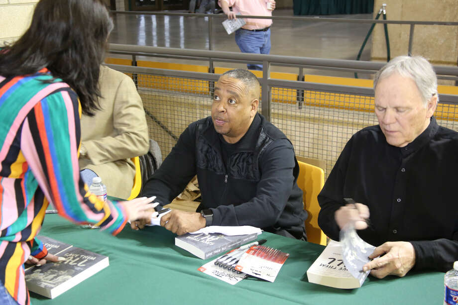 "Former Midland College/NBA star Spud Webb, center, engages with a  fan on Monday night at Chaparral Center during the book signing for Jerry Stone's ""Save Them All: One Coach's Quest."" Stone, right, is shown signing a book. Photo: Forrest Allen