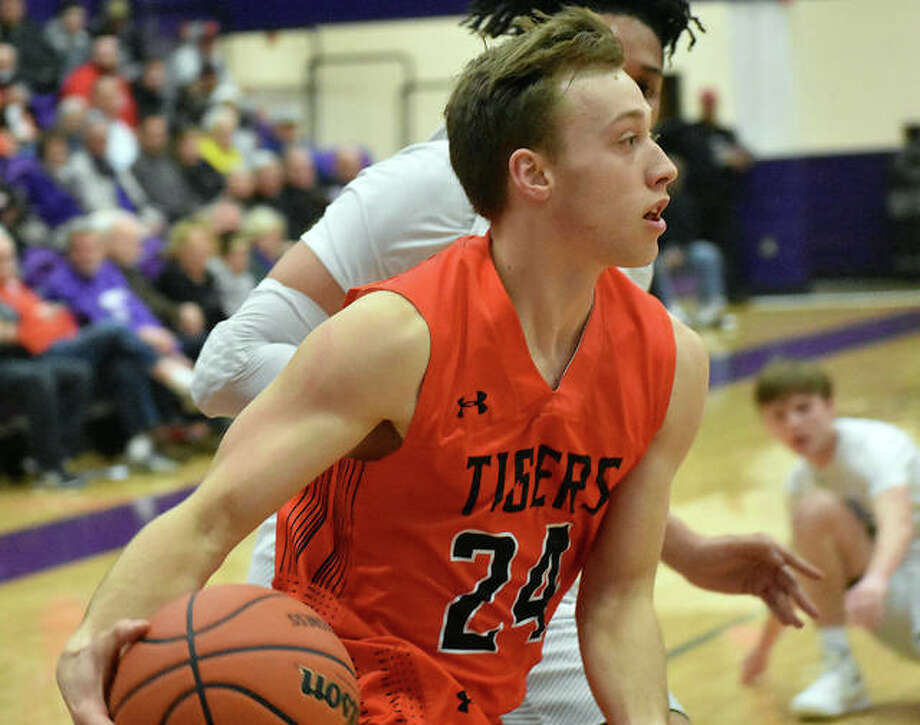 Edwardsville's A.J. Robertson drives baseline and looks for an open teammate during the second quarter against Collinsville.