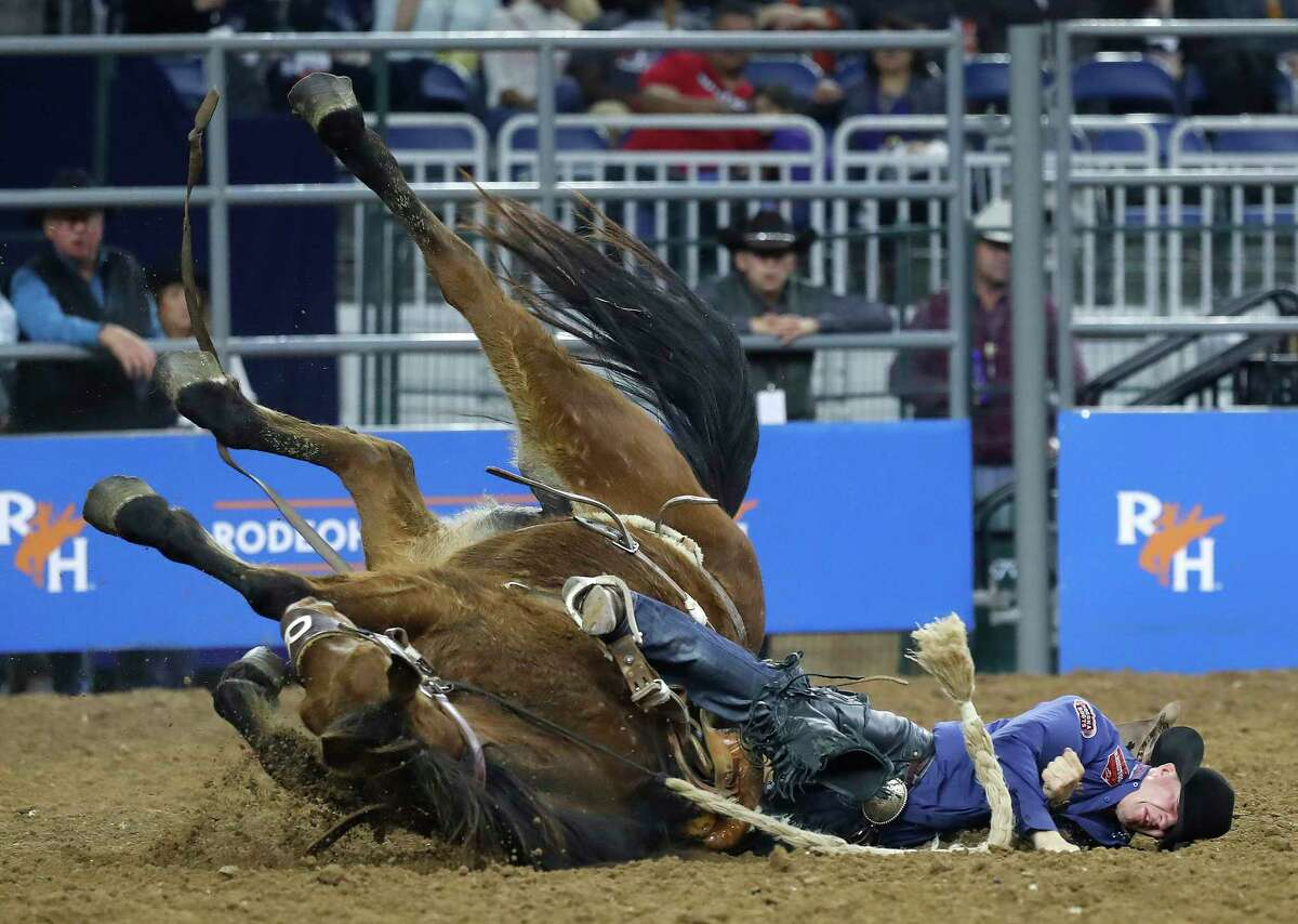 Sterling Crawley falls with New Blood, as the horse slipped and fell as Crawley competed in the saddle bronc riding competition during round 2 of Super Series I of the Houston Livestock Show and Rodeo at NRG Stadium, Tuesday, Feb. 26, 2019, in Houston.