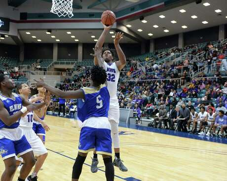 Eddie Lampkin (32) of Morton Ranch attempts a shot over Tyler Callegari (5) of Elkins during the second half of a Class 6A, Region III boy's basketball quarter final game between the Morton Ranch Mavericks and the Elkins Knights on Tuesday, February 26, 2019 at the Merrell Center, Katy, TX.