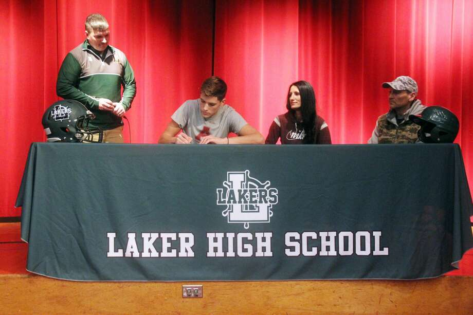 EPBP's Adam Legault signs his letter of intent to play football for Alma College, Friday, at EPBP. Pictured are (from left) EPBP head coach Steve VerBurg, mother Lisa Polega, and father Shane Legault. Photo: Mike Gallagher/Huron Daily Tribune