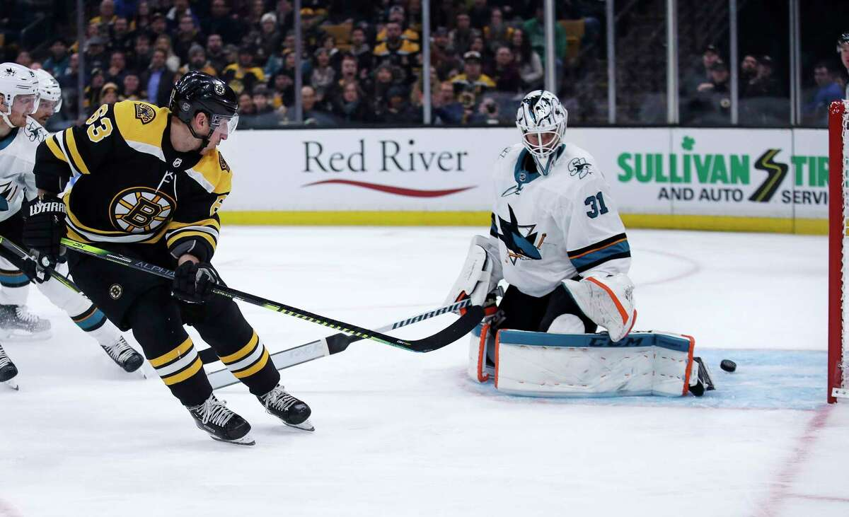 Boston Bruins left wing Brad Marchand, left, scores a goal against San Jose Sharks goaltender Martin Jones, right, during the second period of an NHL hockey game in Boston, Tuesday, Feb. 26, 2019. (AP Photo/Charles Krupa)