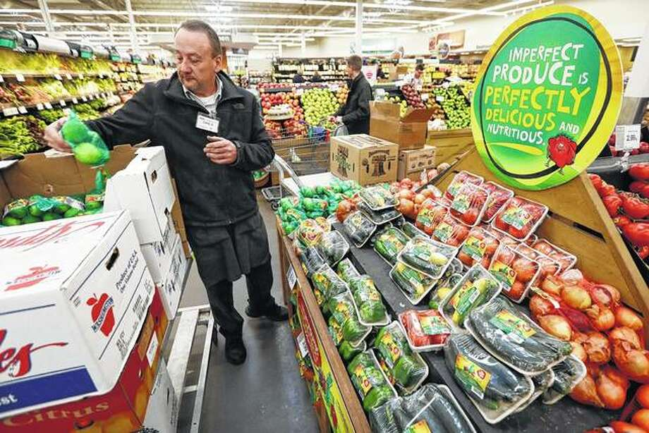 Assistant produce manager Dave Ruble stocks the imperfect produce section in January at the Hy-Vee grocery store in Urbandale, Iowa. After enjoying a brief spotlight in supermarket produce sections, blemished fruits and vegetables already may be getting tossed back in the trash. Photo: Charlie Neibergall   Associated Press