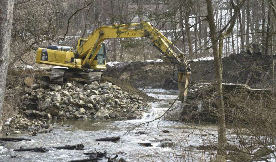 Excavator operator Jarrod Martellacci, works on removing the Old Papermill Dam on the East Aspetuck River. The dam belongs to the Ousatonic Fish & Game Protection Association and its removal is being overseen by the Nature Conservancy. Friday, February 22, 2019, in New Milford, Conn. Photo: H John Voorhees III / Hearst Connecticut Media / The News-Times
