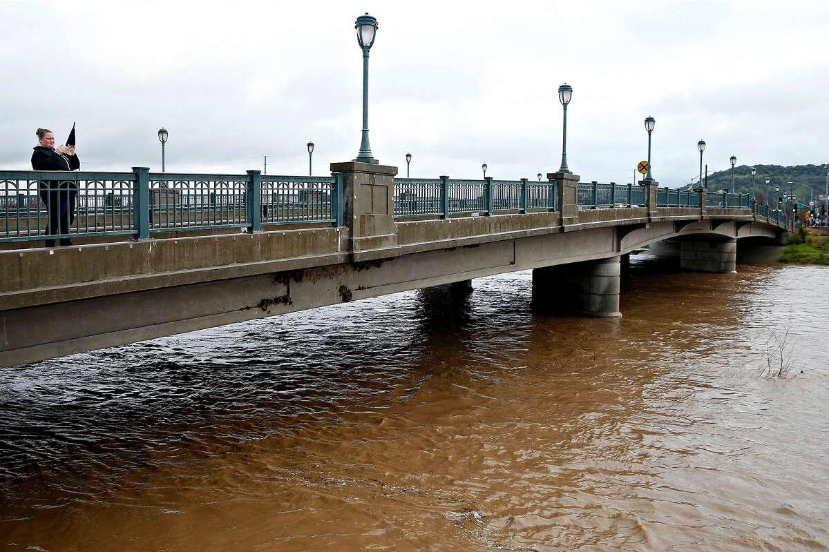 A woman snaps a photo of the Napa River from the First Street bridge between Soscol Ave. and Main St. after the heavy rainstorm in Napa on Feb. 27, 2019.