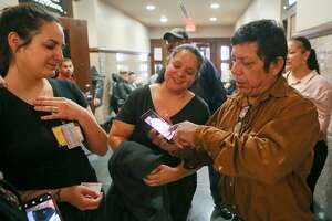 Fernando Yee, from right, maternal grandfather of King Jay Davila, shows a video of his late grandson to family friend Brenda Godinez and Jasmine McGill of King's Angels outside of 227th Criminal District Court, Cadena-Reeves Justice Center, on Feb. 27, 2019. King's Angels is a volunteer group that was formed in the wake of King Jay's death.