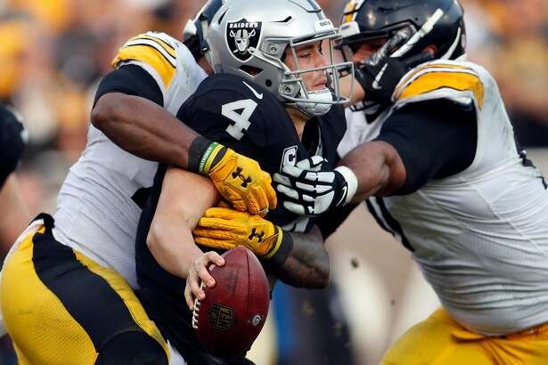 Oakland Raiders' Derek Carr is sacked in 3rd quarter by Pittsburgh Steelers during Raiders' 24-21 win in NFL game at Oakland Coliseum in Oakland, Calif. on Sunday, December 9, 2018.