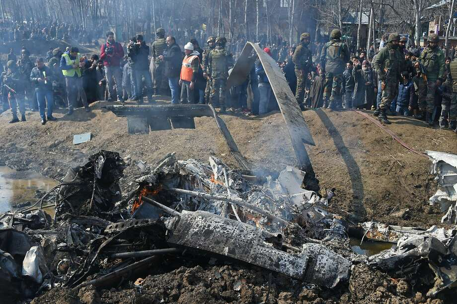 Indian soldiers and Kashmiri onlookers stand near the remains of an Indian Air Force aircraft after it crashed on the outskirts of Srinagar in the disputed region of Kashmir. Photo: Tauseef Mustafa / AFP / Getty Images