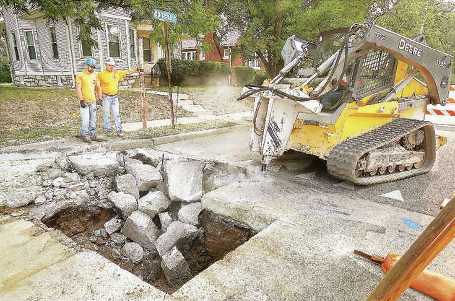 Workers from Loellke Plumbing Inc. in Jerseyville, working with Illinois American Water Company, tear a hole on State House Circle at College Avenue in Alton last August for an improvement project for the water company. The company said it invested about $122 million to install or rehabilitate more than 42 miles of water and sewer main in 2018, in contrast to a recent Illinois Section of American Society of Civil Engineers' (ASCE) Report Card that graded the state's water and wastewater infrastructure systems each with a C- grade. Photo: John Badman | The Telegraph