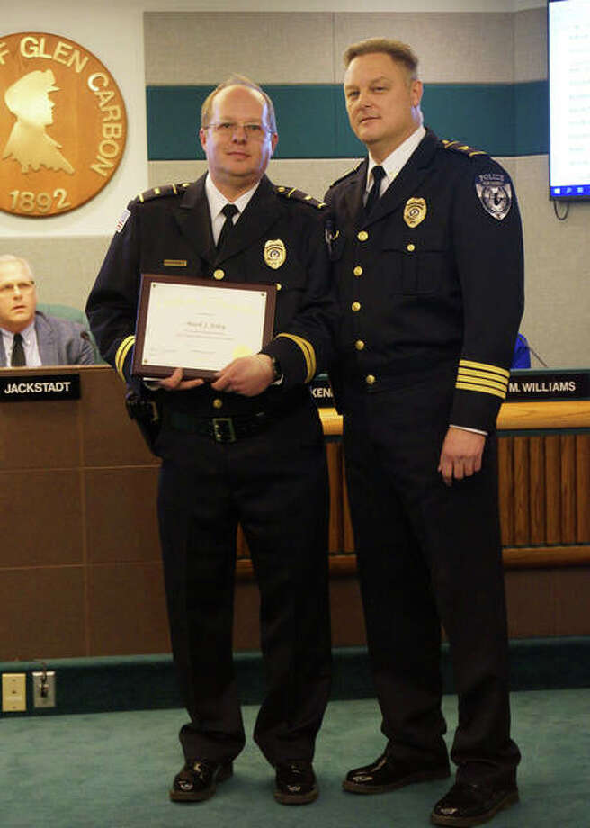 Glen Carbon Police Lt. Mark Foley received a plaque Tuesday, honoring him for 30 years of service to the department. With him is Police Chief Todd Link, right. In the background is Mayor Rob Jackstadt. Photo: Courtesy Of Glen Carbon Police Department