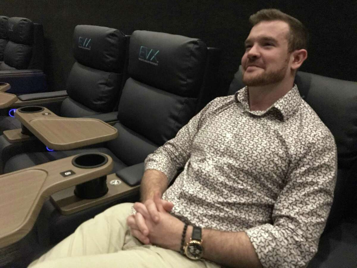 EVO Entertainment Group CEO Mitchell Roberts sits in an auditorium recliner at EVO's new Schertz movie multiplex. The electric-powered recliners include a call button for dine-in service.