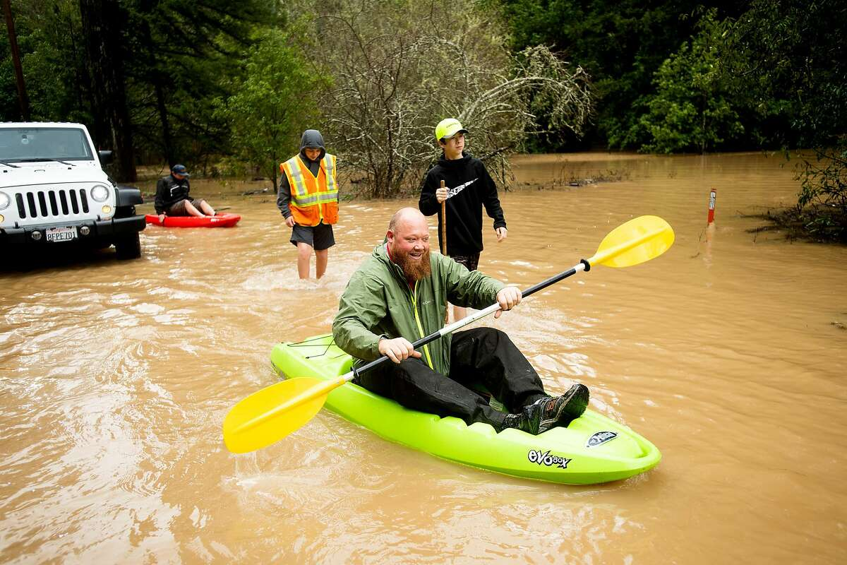 Mitchell Crane canoes along a flooded Highway 116 east of Mays Canyon Rd. as flood waters rise in Guerneville, Calif., on Wednesday, Feb. 27, 2019.