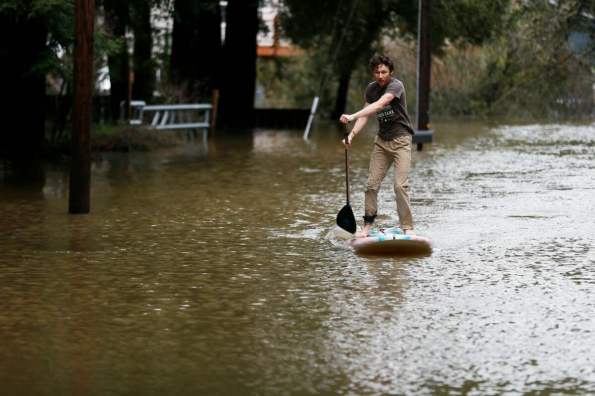 Ziven Posner paddle boards along the flooded Mirabel Road towards Trenton Road on Wednesday, Feb. 27, 2019, in Forestville, Calif.