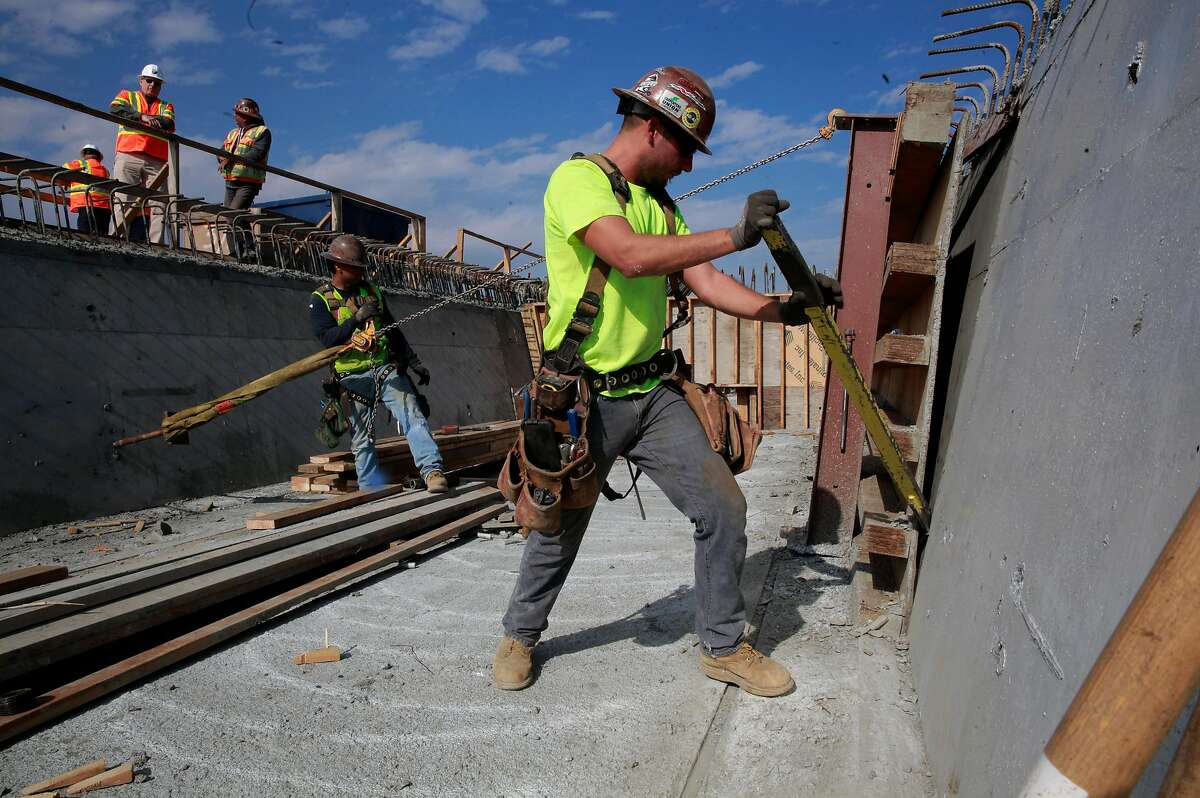 FILE-- Anthony Garcia and fellow workers on an elevated section of tracks of the California high-speed rail system in Fresno, Ca., as seen on Wednesday Feb. 1, 2017. The Trump administration on Thursday followed through with its plan to pull more than $900 million in federal funds from California's beleaguered high-speed rail project.