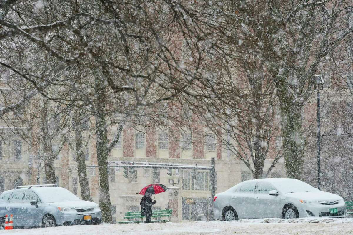 Snow showers are possible Friday morning but meteorologists say warmer temperatures could convert the snow into rain later in the day. In this photograph, a man makes his way up Washington Avenue in Albany as large snow flakes fall on Feb. 27, 2019. (Paul Buckowski/Times Union)